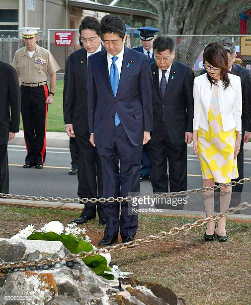 Japanese Prime Minister Shinzo Abe observes a moment of silence after placing a wreath at a memorial to Lt Fusata Iida a Japanese naval pilot who...