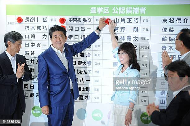 Japanese Prime Minister Shinzo Abe of the Liberal Democratic Party places roses above names of elected candidate of the party at the head quarter of...