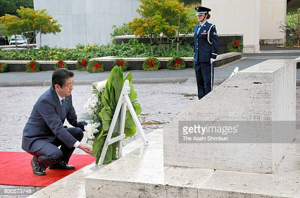 Japanese Prime Minister Shinzo Abe offers a wreath at the National Memorial Cemetery of the Pacific on December 26 2016 in Honolulu Hawaii On...