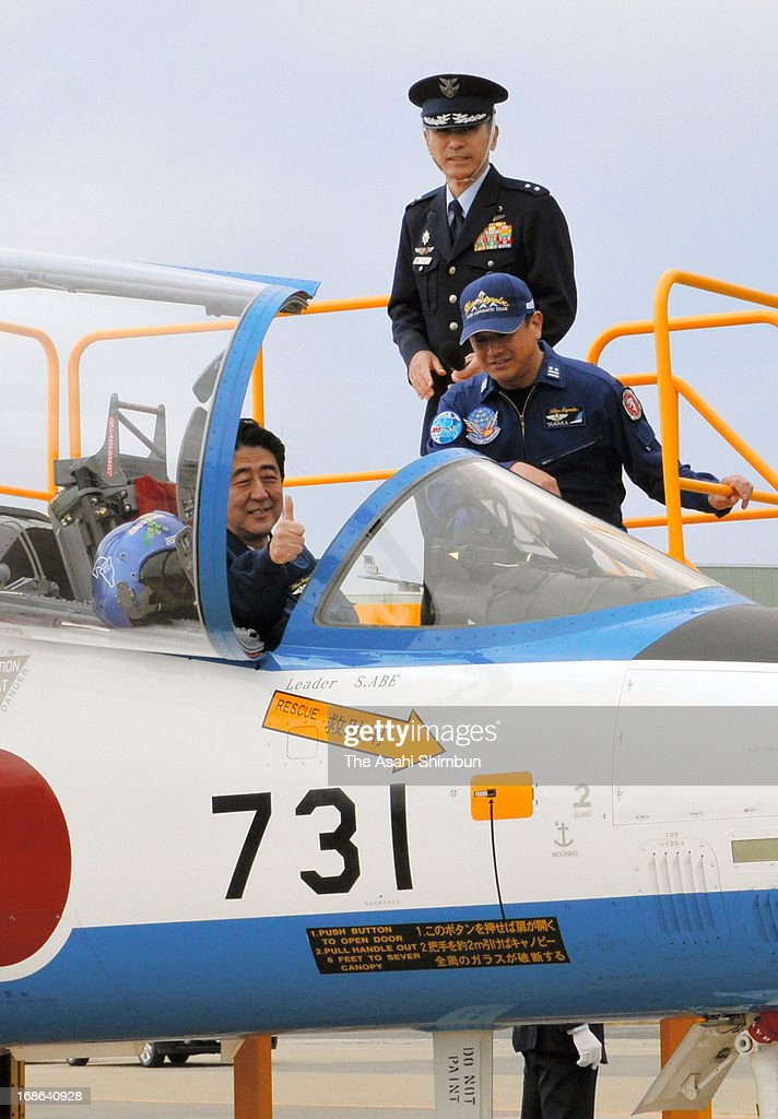 Japanese Prime Minister Shinzo Abe poses for photographs at the cockpit of a T-4 training aircraft of the Japan Air Self-Defense Force acrobat team 'Blue Impulse' at the JASDF Higashimatsushima Base on May 12, 2013 in Higashimatsushima, Miyagi, Japan. Abe inspects the restoration from the Great East Japan Earthquake and following tsunami.