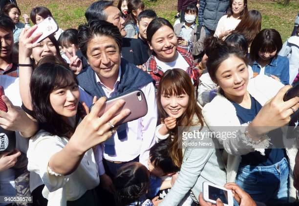 Japanese Prime Minister Shinzo Abe poses for selfies during a walk in Tokyo's Yoyogi Park on April 1 2018 ==Kyodo