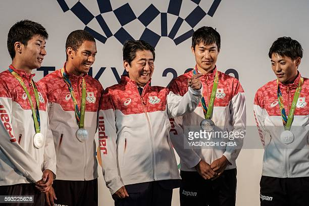 Japanese Prime Minister Shinzo Abe poses with Japanese athletes won the silver medal for men's 100m x 4 relay as he celebrates with Olympic medalists...