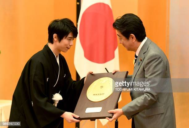 Japanese Prime Minister Shinzo Abe presents the People's Honor Award trophy to Japanese figure skater Yuzuru Hanyu during its presentation ceremony...