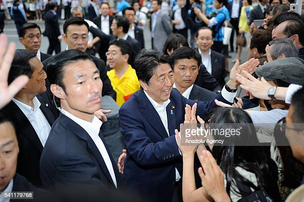 Japanese Prime Minister Shinzo Abe, president of the ruling Liberal Democratic Party, greets the voters during the July 10 Upper House election...