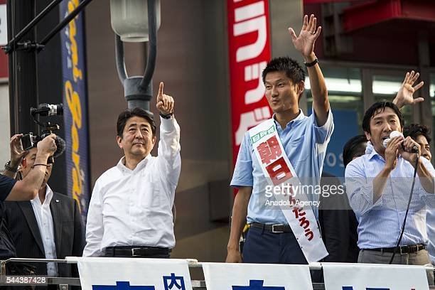 Japanese Prime Minister Shinzo Abe President of the ruling Liberal Democratic Party and candidate Kentaro Asahi salute the voters during the July 10...