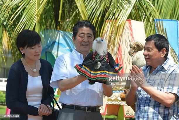 TOPSHOT Japanese Prime Minister Shinzo Abe raises a Philippine eagle stuffed toy as Philippine President Rodrigo Duterte applauds during the naming...
