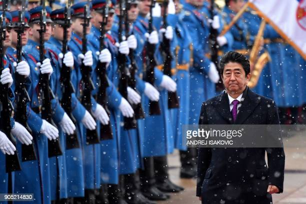 Japanese Prime Minister Shinzo Abe reviews a guard of honour next to Serbian President as snow falls prior their meeting in Belgrade on January 15...
