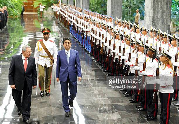 Japanese Prime Minister Shinzo Abe reviews a honour guard along with Cuban President Raul Castro during a welcome ceremony at the Council of State on...