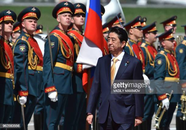Japanese Prime Minister Shinzo Abe reviews a Russian honour guard during a welcoming ceremony upon his arrival at Vnukovo Airport on May 26 2018