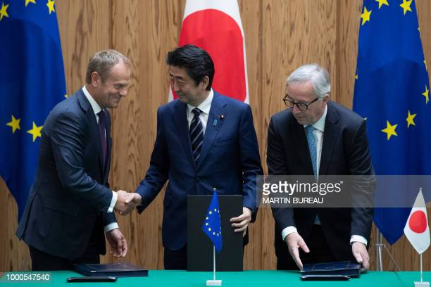 TOPSHOT Japanese Prime Minister Shinzo Abe shakes hands with European Council President Donald Tusk as European Commission President JeanClaude...