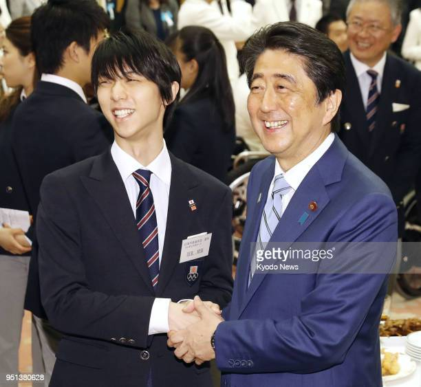 Japanese Prime Minister Shinzo Abe shakes hands with Pyeongchang Olympics figure skating gold medalist Yuzuru Hanyu at a reception held at the prime...