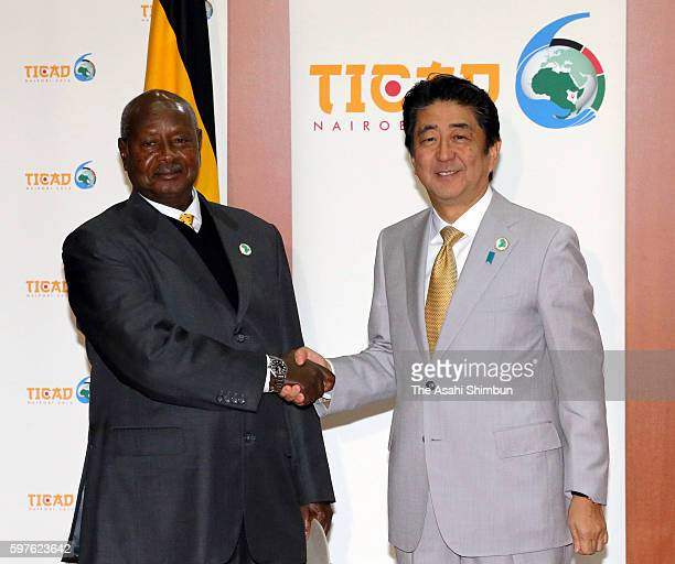 Japanese Prime Minister Shinzo Abe shakes hands with Uganda President Yoweri Museveni prior to their meeting on the sidelines of the Tokyo...