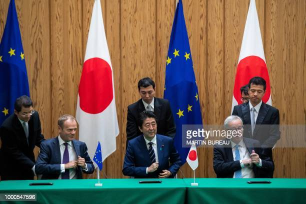 TOPSHOT Japanese Prime Minister Shinzo Abe signs an agreement with European Council President Donald Tusk and European Commission President...