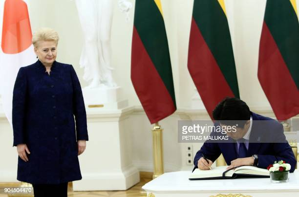 Japanese Prime Minister Shinzo Abe signs the guest book during a meeting with Lithuanian President Dalia Grybauskaite in Vilnius on January 13 2018...