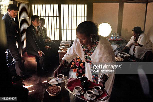 Japanese Prime Minister Shinzo Abe sits with Ethiopian President Mulatu Teshome as they attend a traditional coffee ceremony in the Japanese garden...