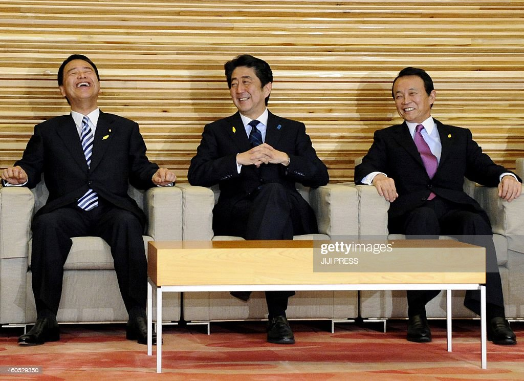Japanese Prime Minister Shinzo Abe (C) smiles alongside Finance Minister Taro Aso (R) and Economic Revitalization Minister Akira Amari (L) at a cabinet meeting at Abe's office in Tokyo on December 16, 2014. Abe stepped up pressure on business leaders to hike wages as he embarked on a renewed push to reinvigorate Japan's economy after his weekend election triumph. Stagnant salaries are one of the main missing links in the 'virtuous circle' of growth that the premier's signature 'Abenomics' plan envisages.