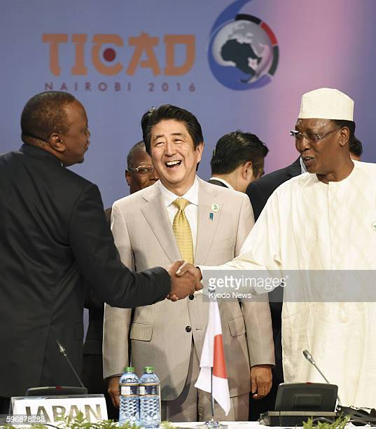Japanese Prime Minister Shinzo Abe smiles as Kenyan President Uhuru Kenyatta and Idriss Deby Itno Chad's president and current African Union chief...