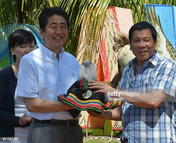 Japanese Prime Minister Shinzo Abe smiles as Philippine President Rodrigo Duterte hands over a gift of a Philippine eagle stuffed toy during a...