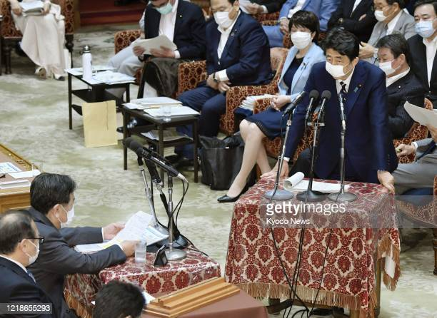 Japanese Prime Minister Shinzo Abe speaks at a session of the House of Representatives budget committee in Tokyo on June 9 wearing a face mask amid...