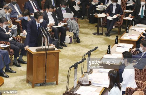 Japanese Prime Minister Shinzo Abe speaks during a meeting of the House of Councillors budget committee in Tokyo on June 11 wearing a face mask amid...