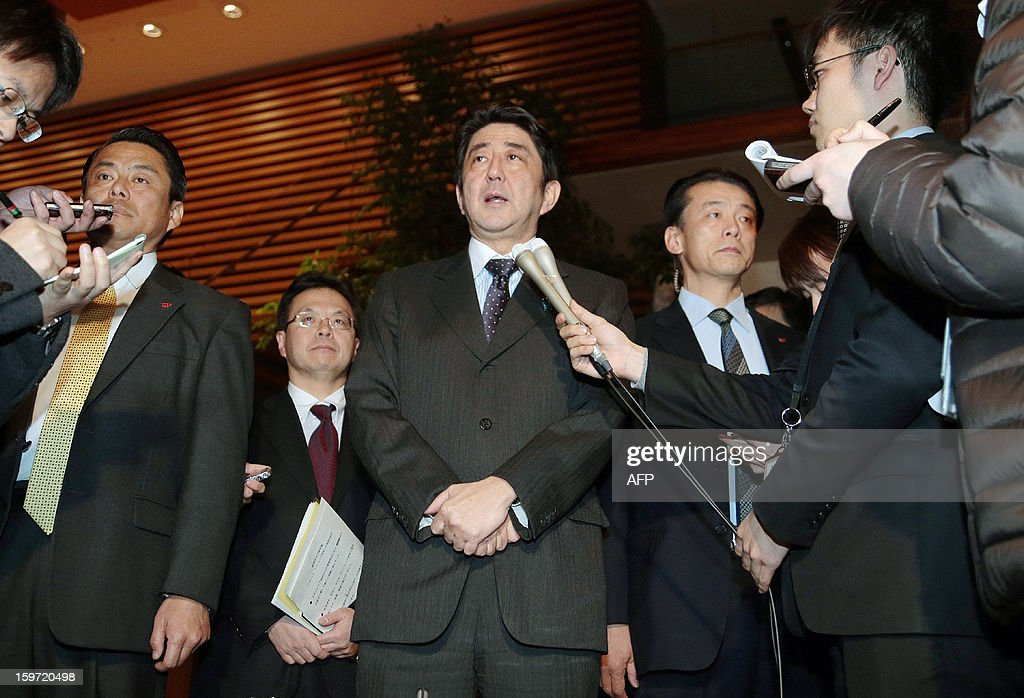 Japanese Prime Minister Shinzo Abe (C) speaks to reporters outside his office in Tokyo after a telephone conversation with his Algerian counterpart Abdelmalek Sellal on January 20, 2013. Prime Minister Shinzo Abe on Saturday ordered his government to do everything possible to ensure the safety of 10 Japanese unaccounted for in the 'despicable' hostage-taking in Algeria. Energy giant BP said Saturday that four of its employees remained missing following the attack on the In Amenas gas plant in Algeria, and CEO Bob Dudley said he feared for their lives.