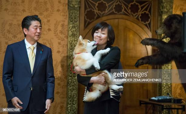 Japanese Prime Minister Shinzo Abe stands by his wife Akie Abe as she holds an Akita Inu puppy named Masaru in her ams during their official visit to...