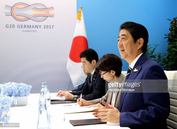 Japanese Prime Minister Shinzo Abe talks to South Korean President Moon Jaein during their bilateral meeting on the sidelines of the G20 Summit on...