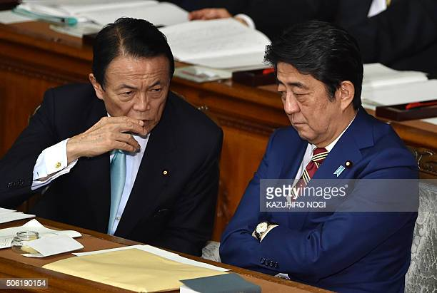 Japanese Prime Minister Shinzo Abe talks with Finance Minister Taro Aso during a plenary session of the House of Representatives at the Diet in Tokyo...
