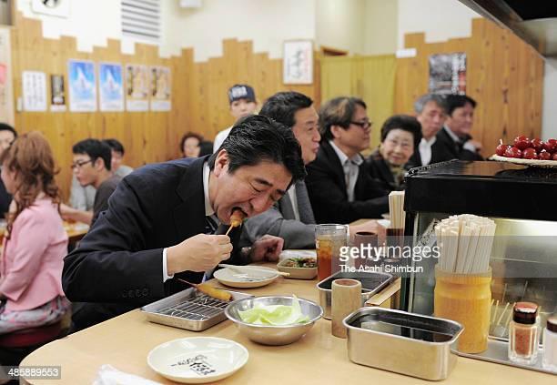 Japanese Prime Minister Shinzo Abe tastes the 'Kushikatsu' local Osaka cuisine deepfried cutlet on April 18 2014 in Osaka Japan Abe is in Osaka to...