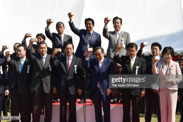 Japanese Prime Minister Shinzo Abe toast 'masu' Japanese wooden sake glass with lawmakers during the cherry blossom viewing party at Shinjuku Gyoen...