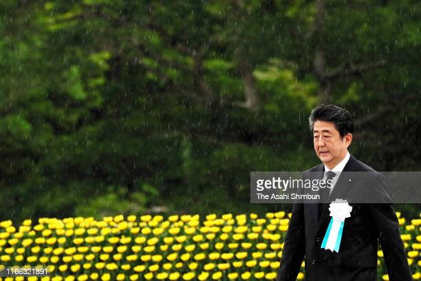 Japanese Prime Minister Shinzo Abe walks after his remarks during the Peace Memorial Ceremony on the 74th anniversary of the atomic bombing of...