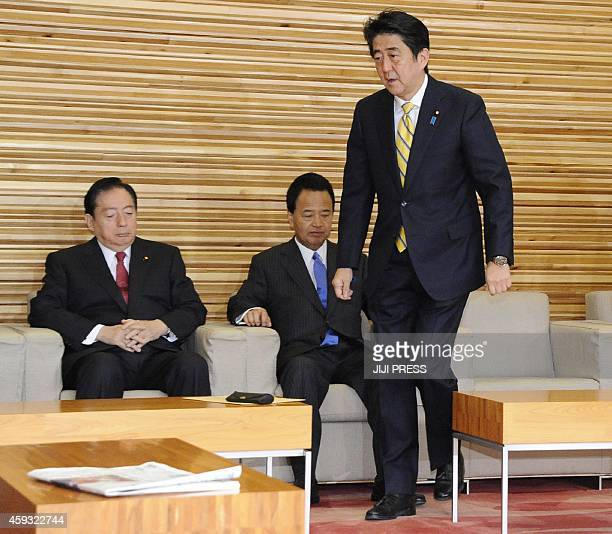 Japanese Prime Minister Shinzo Abe walks in front of Japanese Land Infrastructure Transport and Tourism Minister Akihiro Ota and Japanese Economic...
