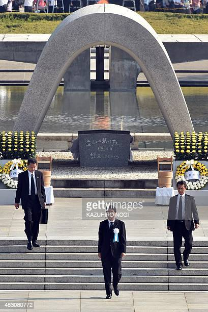 Japanese Prime Minister Shinzo Abe walks in front of the memorial cenotaph for victims of a 1945 atomic bombing during a memorial ceremony to mark...