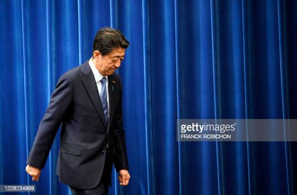 Japanese Prime Minister Shinzo Abe walks outat the end of his press conference at the prime minister official residence in Tokyo on August 28, 2020....