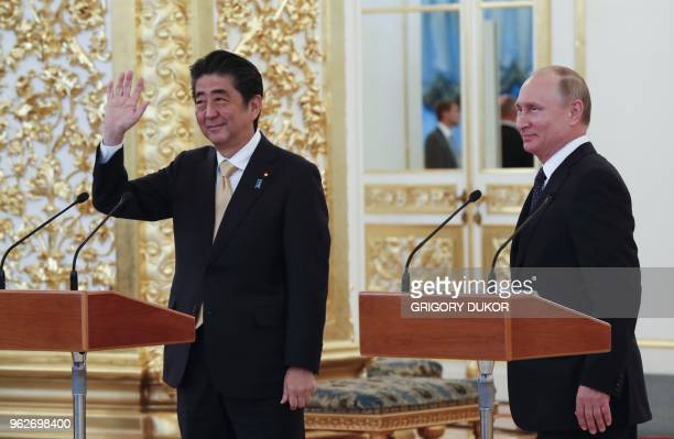 Japanese Prime Minister Shinzo Abe waves as he attends with Russian President Vladimir Putin a communication session with the crew of the...