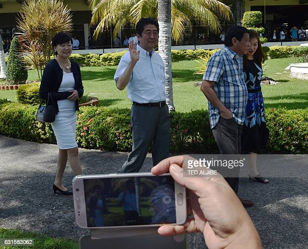 Japanese Prime Minister Shinzo Abe waves as he walks with Philippine President Rodrigo Duterte and their wives Akie and Honeylet on their way to the...