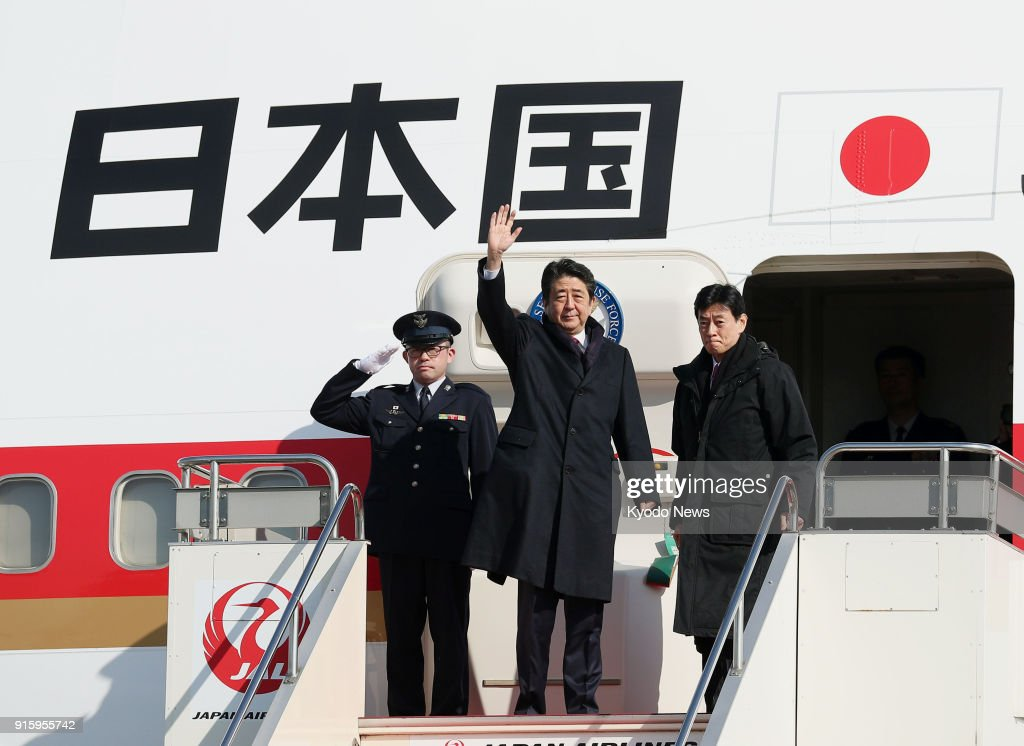 Japanese Prime Minister Shinzo Abe (C) waves at Haneda airport in Tokyo on Feb. 9, 2018, as he leaves for South Korea to attend the opening ceremony of the Pyeongchang Olympics. ==Kyodo