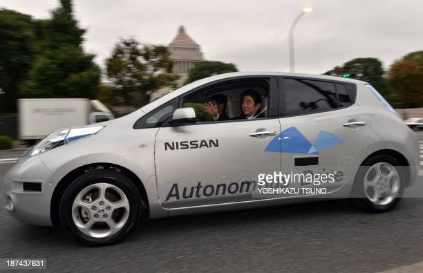 Japanese Prime Minister Shinzo Abe waves during a test drive of Japanese auto maker Nissan Motor's autonomous vehicle in Tokyo on November 9 2013 Abe...