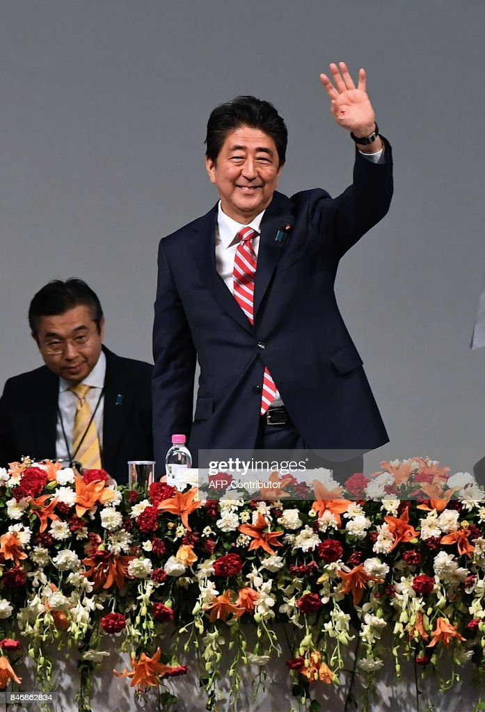 Japanese Prime Minister Shinzo Abe waves during the India-Japan Business plenary session during the India-Japan Buissness Plenary session at the India-Japan Annual summit at Mahatama Mandir convention center in Gandhinagar on September 14, 2017. Japan's Prime Minister Abe on September 14 inaugurated India's first bullet train project -- a $19 billion line in the home state of Indian leader Modi intended to revitalise the country's vast but dilapidated network. /