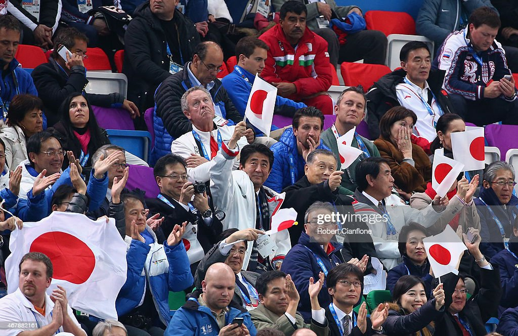 Japanese Prime Minister Shinzo Abe (C) waves the national flag as he watches the Figure Skating Team Ladies Short Program with former Prime Minister and President of Tokyo 2020 Organising Committee President Yoshiro Mori (C-R) during day one of the Sochi 2014 Winter Olympics at Iceberg Skating Palace on February 8, 2014 in Sochi, Russia.