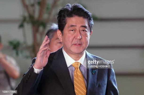 Japanese Prime Minister Shinzo Abe waves to journalists from his official residence in Tokyo on September 18, 2018.