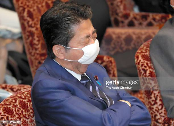 Japanese Prime Minister Shinzo Abe wearing a face mask yawns during the Upper House Audit Committee at the Diet on April 1, 2020 in Tokyo, Japan. Abe...