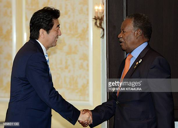 Japanese Prime Minister Shinzo Abe welcomes Zambia's President Michael Sata as he arrives for their bilateral meeting at the fifth Tokyo...