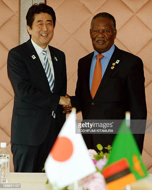 Japanese Prime Minister Shinzo Abe welcomes Zambia's President Michael Sata during their bilateral meeting at the fifth Tokyo International...