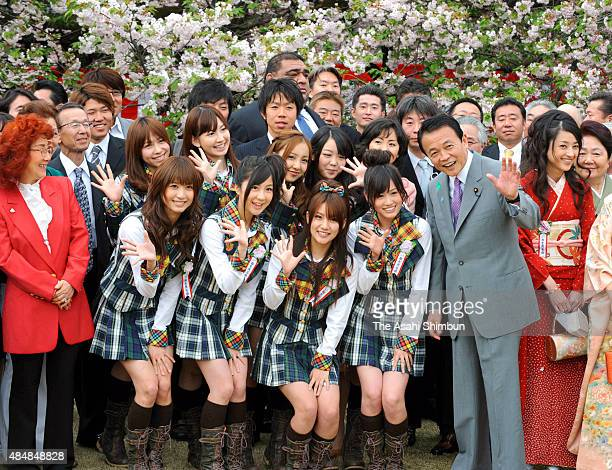 Japanese Prime Minister Taro Aso poses for photographs with members of idol group AKB48 during the cherry blossom viewing party at Shinjuku Gyoen...