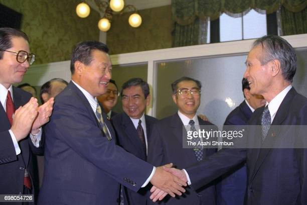 Japanese Prime Minister Tomiichi Murayama shakes hands with coalition Liberal Democratic Party secretary general Yoshiro Mori after the noconfidence...