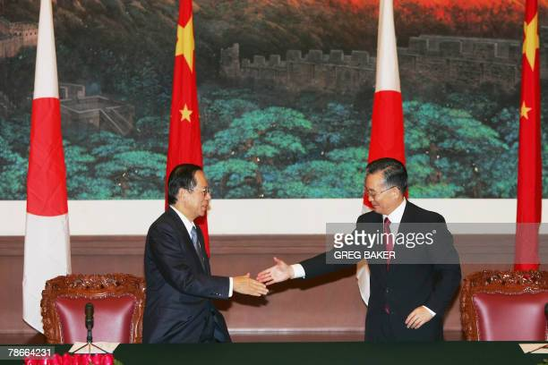 Japanese Prime Minister Yasuo Fukuda shakes hands with Chinese Premier Wen Jiabao after their joint press briefing in Beijing's Great Hall of the...