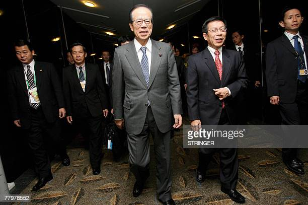 Japanese Prime Minister Yasuo Fukuda walks along the aerobridge with Singapore's Minister for National Development Mah Bow Tan upon his arrival at...