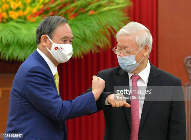 Japanese Prime Minister Yoshihide Suga and Nguyen Phu Trong, General Secretary of the Communist Party of Vietnam fist bumps prior to their meeting at...