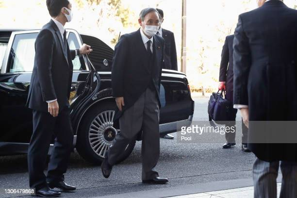 Japanese Prime Minister Yoshihide Suga wearing a face mask arrives at the National Theatre of Japan to attend the national memorial service for the...